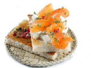 Tostadas de pan con queso crema y salmón ahumado con cebollino y 5 bayas