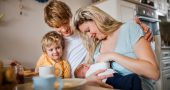 Young parents with newborn baby and small toddler son at home.