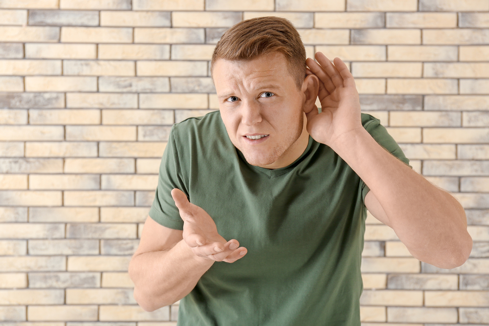 Young man with hearing problem on brick wall background