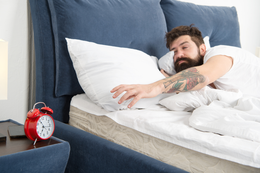 Overslept again. Tips for waking up early. Man bearded hipster sleepy face bed with alarm clock. Turn off that ringing. What terrible noise. Problem early morning awakening. Get up with alarm clock