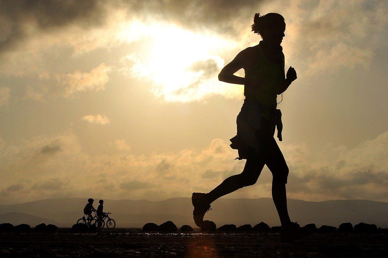 Mujer runner corre al atardecer