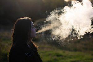 Joven vapeando cigarro electrónico
