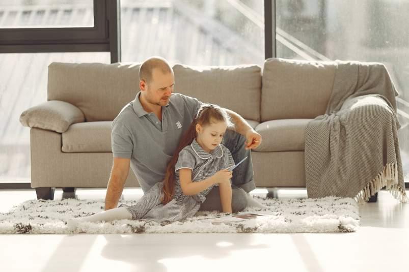 Nina jugando con su padre en casa durante la cuarentena